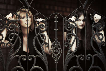 clinging: Two sad young women at the iron fence