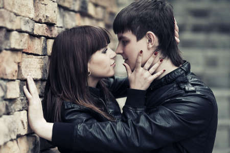 Happy young couple in love at the brick wall photo