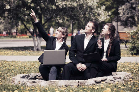 Young business people with laptop in a city park photo