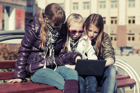 Teenage school girls using laptop on the bench photo