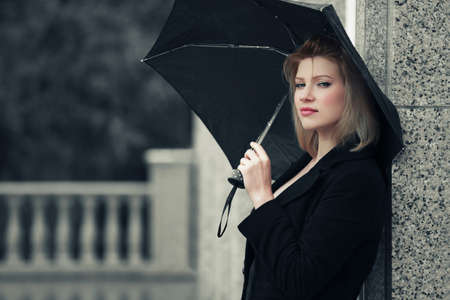 Young fashion woman with umbrella at the wall photo