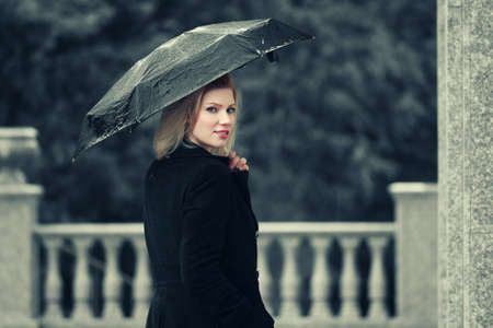 Happy young fashion woman with umbrella in the rain photo