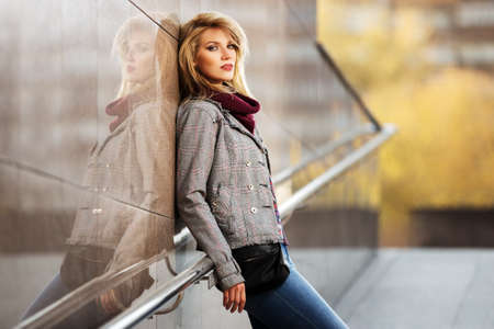 Young fashion blond woman standing at the wall