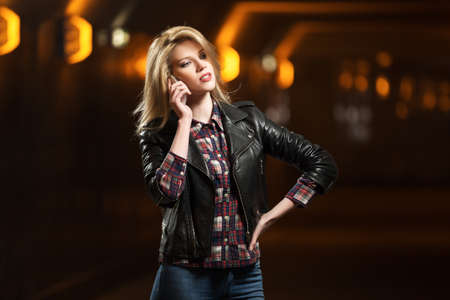 Young fashion blond woman in leather jacket calling on mobile phone photo