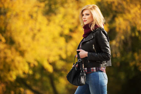 Young fashion blond woman in leather jacket in autumn park photo
