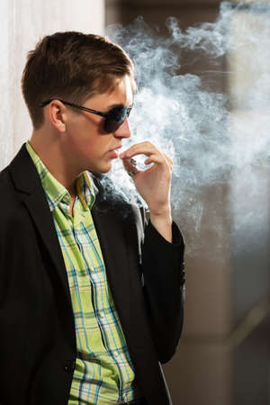 cigarette smoke: Young fashion man in sunglasses smoking a cigarette