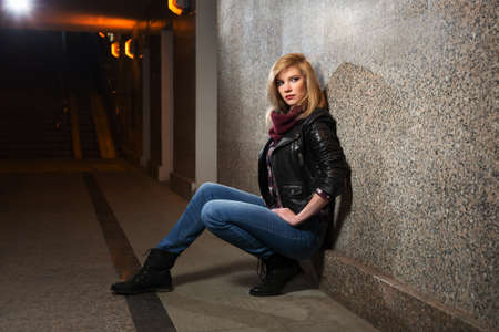 leather coat: Young fashion woman in leather jacket sitting at the wall