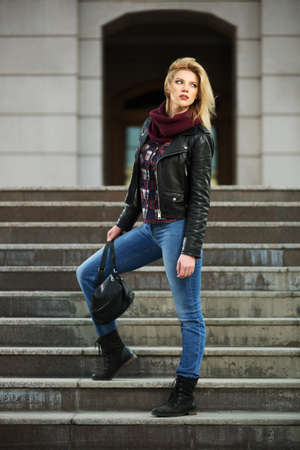 leather coat: Young fashion blond woman in leather jacket on the steps