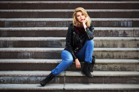 Young fashion blond woman in leather jacket sitting on the steps photo