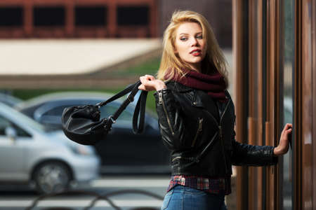 Young fashion blond woman with handbag at the mall door Foto de archivo