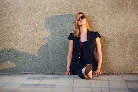 depressed woman: Sad young fashion blond woman in sunglasses sitting at the wall Stock Photo