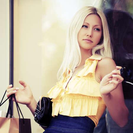 mujer elegante: Moda mujer rubia con bolsas de compras en el centro comercial