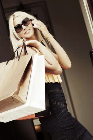 Fashion woman with shopping bags calling on the phone Standard-Bild