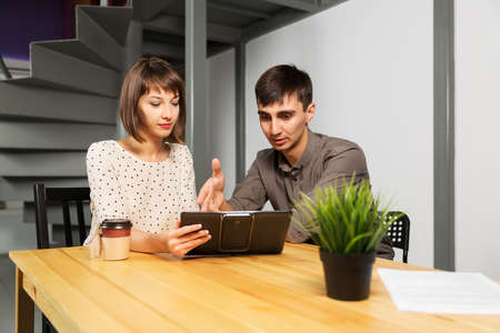Young couple with tablet computer sitting at the table photo