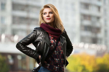 leather coat: Young fashion blond woman in leather jacket on the city street