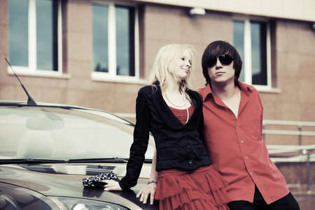 Happy young couple in love by new car photo