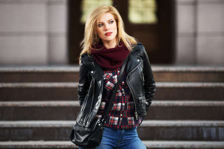 female pose: Young fashion blond woman in leather jacket on the steps