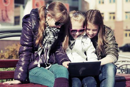 Teenage school girls using laptop on the bench photo