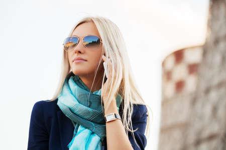 donne eleganti: Donna bionda di affari di moda chiamare sul cellulare all'aperto