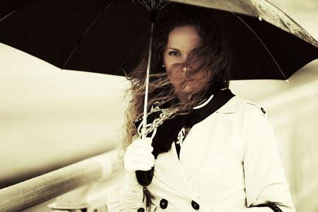 glamour woman elegant: Sad beautiful fashion woman with umbrella in the wind Stock Photo
