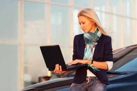 donne eleganti: Giovane donna d'affari di modo con il computer portatile dalla sua auto Archivio Fotografico