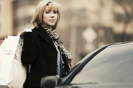 Young fashion woman with shopping bags on the car parking photo