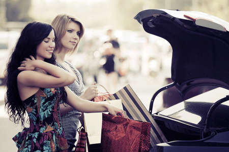 Two young women with shopping bags on the car parking photo