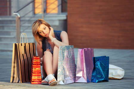 shopping girl: Sad young fashion woman with shopping bags sitting on a sidewalk Stock Photo