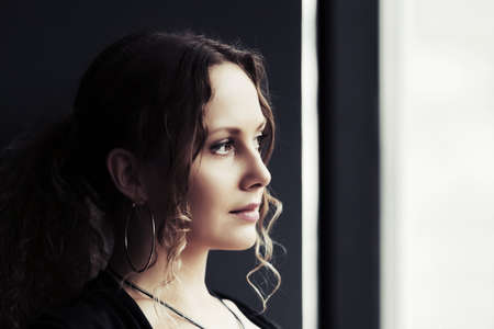 Sad beautiful woman looking out the window