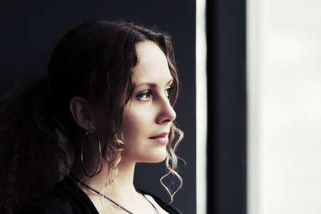 through window: Sad beautiful woman looking out the window
