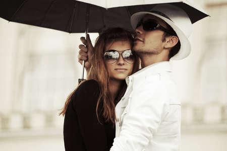uomo sotto la pioggia: Moda giovane coppia in amore con esterno ombrello