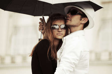 male friends: Young fashion couple in love with umbrella outdoor