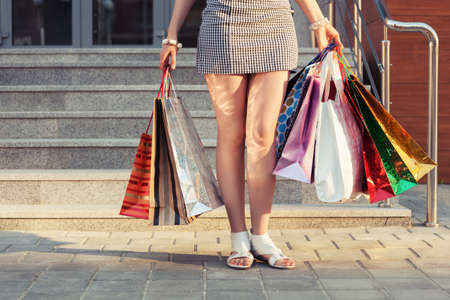 Woman with shopping bags against a mall steps