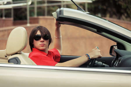 convertible: Young man in sunglasses driving convertible car Stock Photo