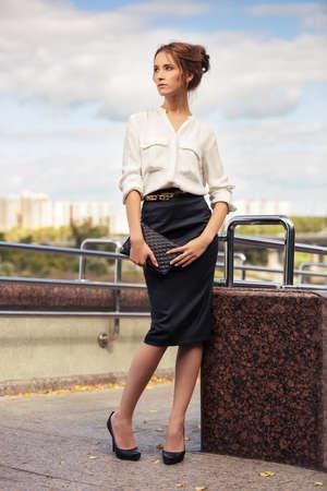 mujer elegante: Mujer de negocios joven de la manera con el bolso que recorre en la calle de la ciudad
