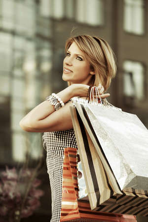 gift bags: Happy young woman with shopping bags against mall window Stock Photo