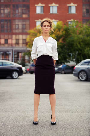 models posing: Young fashion business woman standing on the car parking