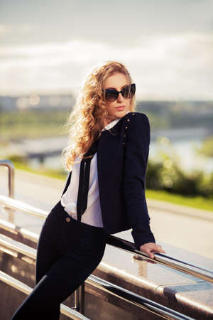 capelli biondi: Moda giovane donna in occhiali da sole sulla strada della citt�
