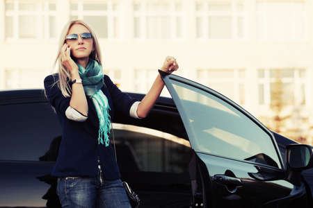 Fashion business woman calling on the cell phone at the car