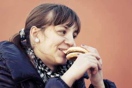fat food: Teenage girl eating a burger
