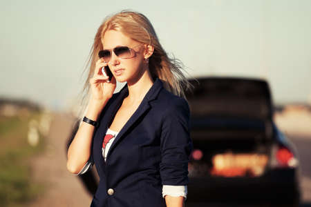 broken car: Young fashion woman with broken car calling on the cell phone Stock Photo