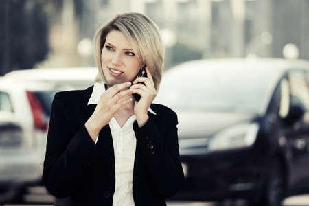 llamando: Mujer de negocios joven que llama por el teléfono celular