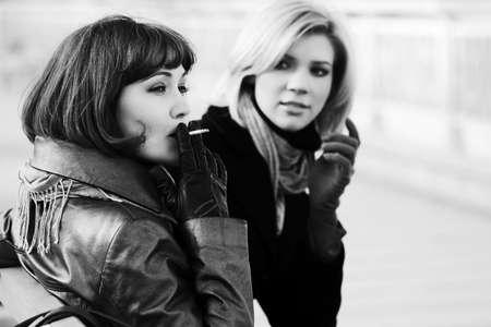 women smoking: Two happy young fashion women smoking on the bench