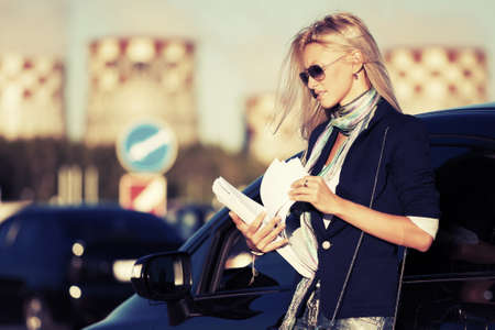 blonde females: Fashion business woman with financial papers at the car