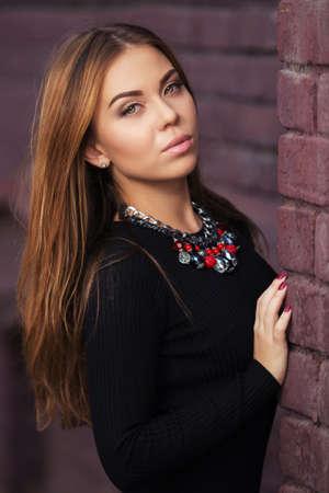 cabello negro: Mujer de moda joven en el vestido negro en la pared de ladrillo