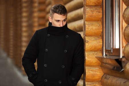 modelos hombres: Hombre hermoso joven en el cl�sico abrigo negro de pie en la pared de madera Foto de archivo