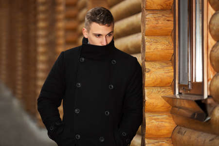 model male: Young handsome man in classic black coat standing at the wooden wall