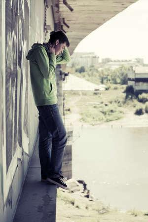 gente triste: El hombre joven en la depresi�n de pie sobre el puente del r�o