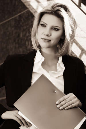 file clerks: Happy young business woman with a folder at office building