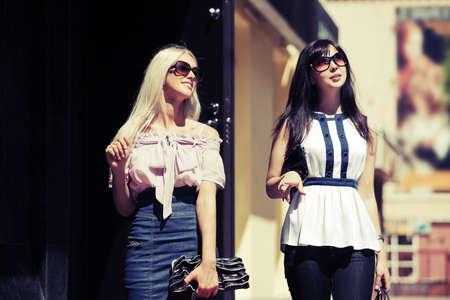 Dos mujeres jovenes de la manera que caminan por la calle de la ciudad